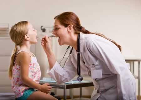 Doctor giving girl checkup in doctor office