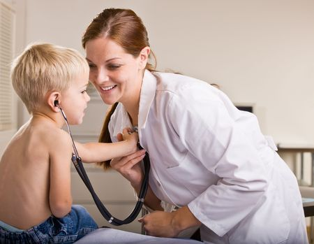 stethoscope: Doctor giving boy checkup in doctor office