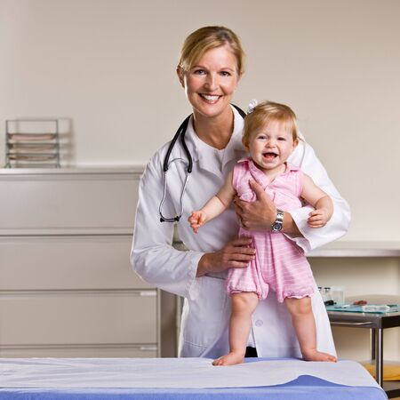 Doctor and baby girl in doctor office photo