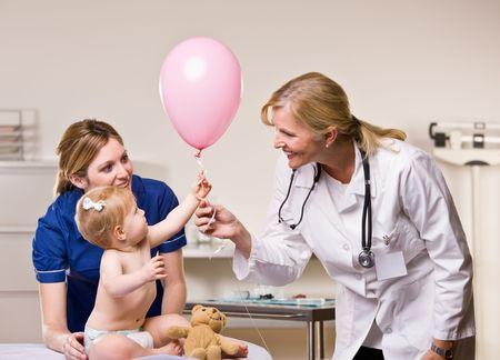 Doctor handing baby girl balloon photo