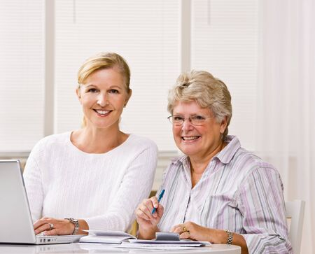 Senior woman writing checks with daughter help photo