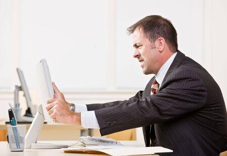 frustrating: Businessman adjusting computer monitor