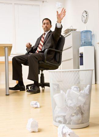 Zakenman die document in afvalmand werpen