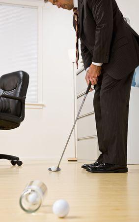 Uomo d'affari mettendo palla da golf in ufficio Archivio Fotografico