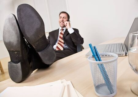 Businessman talking on telephone with feet up photo