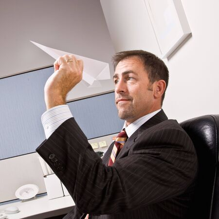 Businessman throwing paper airplane photo