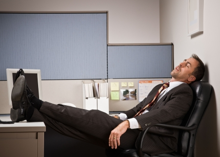 Businessman sleeping at desk with feet up photo