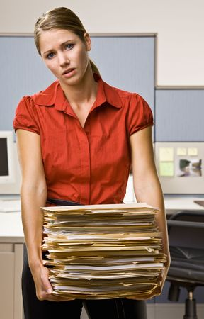 frustrating: Businesswoman carrying stack of file folders