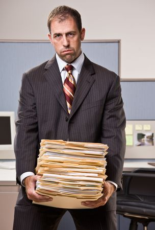 heavy: Businessman carrying stack of file folders Stock Photo