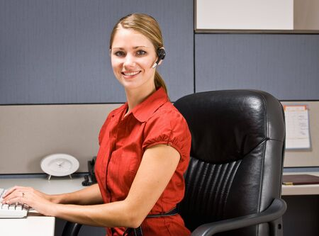 Businesswoman talking on headset at desk