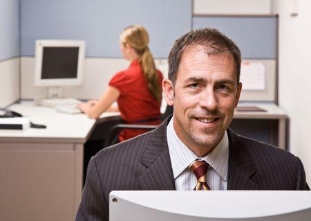 Businessman sitting at desk smiling photo