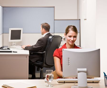 office cubicle: Businesswoman typing on computer at desk