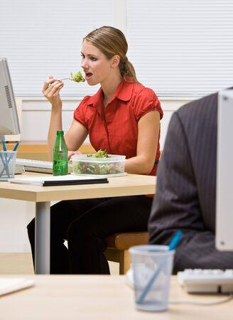 Businesswoman eating salad at desk photo