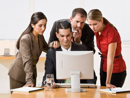 evaluating: Business people looking at computer