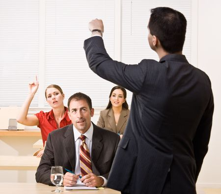 Businessman answering questions in meeting photo