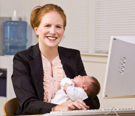 Businesswoman holding baby at desk Foto de archivo
