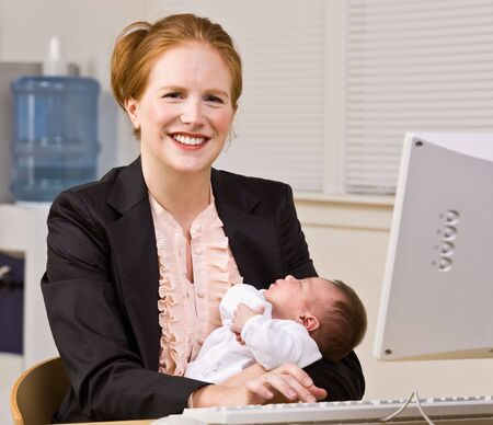 Businesswoman holding baby at desk photo