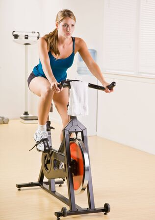 stationary bike: Woman riding stationary bicycle in health club