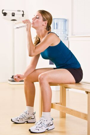 Woman drinking water in health club Stock Photo - 6582335