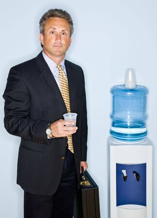 Businessman drinking water from water cooler photo