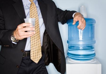Businessman drinking water from water cooler Foto de archivo