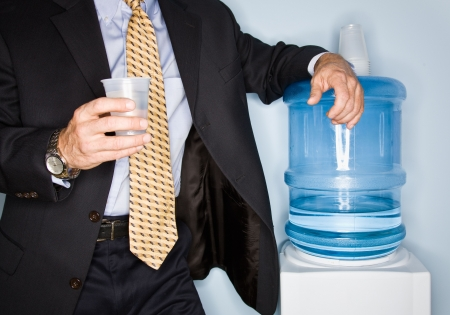 Businessman drinking water from water cooler Banque d'images