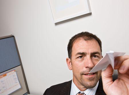 Businessman throwing paper airplane photo