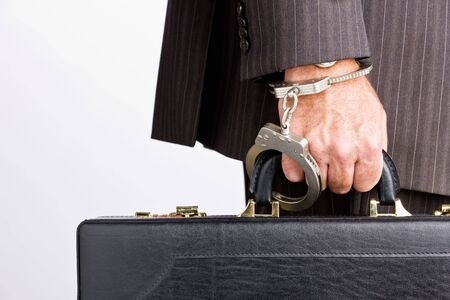 Businessman handcuffed to briefcase Stock Photo