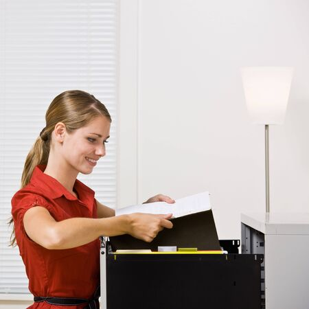 office cabinet: Businesswoman putting file in file cabinet