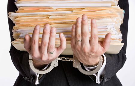 handcuffing: Businessman in handcuffs holding file folders Stock Photo