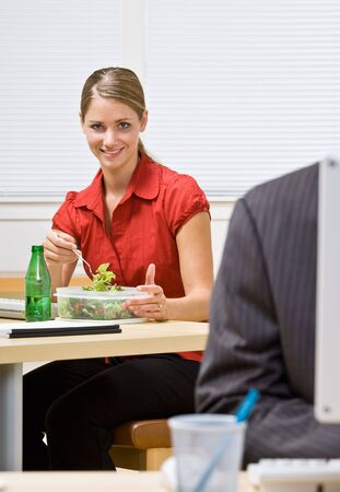 Businesswoman eating salad at desk Stock Photo