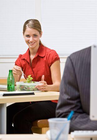 office desk: Businesswoman eating salad at desk Stock Photo