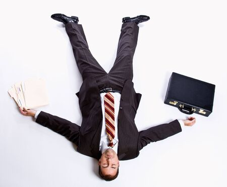 Businessman laying on floor and briefcase Standard-Bild