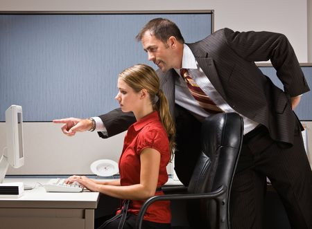 Businessman pointing at co-workers computer photo