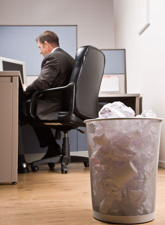 Businessman at desk and trash basket photo