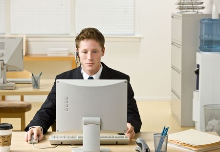 Businessman in headset working at computer photo