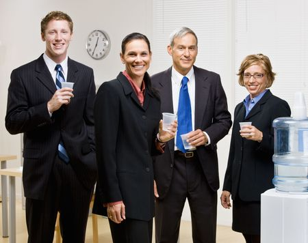 Business people drinking water at water cooler photo