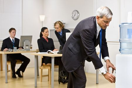 Businessman getting water from water cooler Stock Photo - 6583459