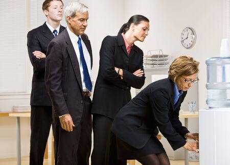 cooler: Business people waiting turn at water cooler Stock Photo