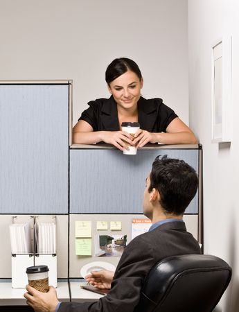 Co-workers talking in office cubicle photo