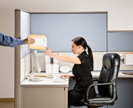 Businesswoman multi-tasking at desk in cubicle photo