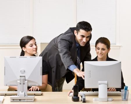 Businessman helping co-worker with work Foto de archivo