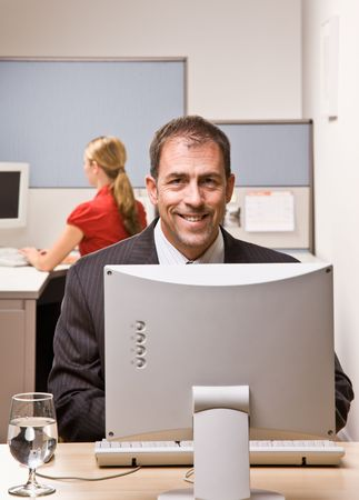 Businessman typing on computer at desk photo