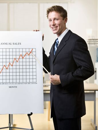 motioning: Businessman pointing to chart