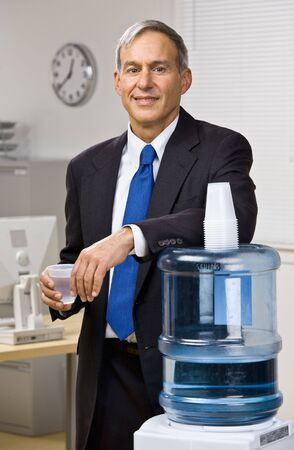 Businessman getting water from water cooler photo