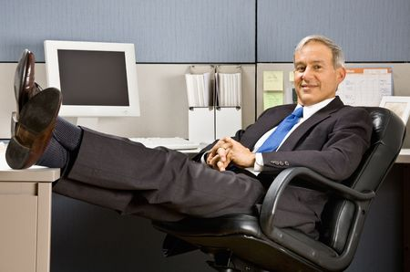 old furniture: Businessman with feet up at desk