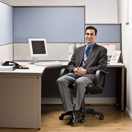 Businessman sitting at desk in cubicle