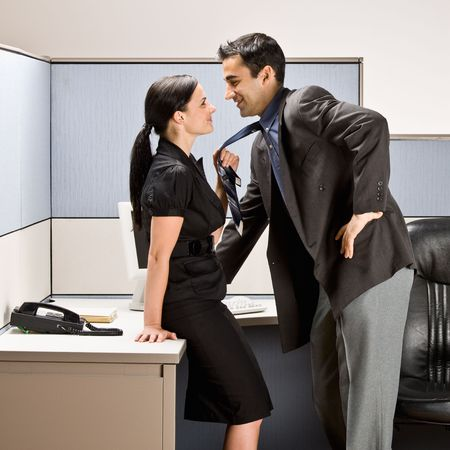 Co-workers kissing in office cubicle photo