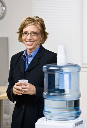 Businesswoman getting water from water cooler photo