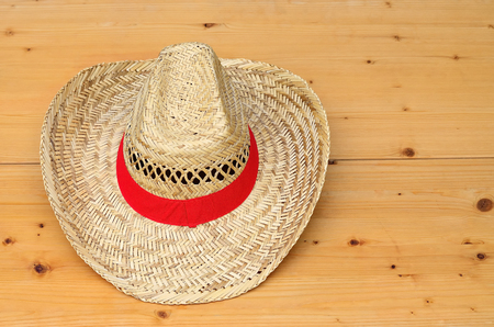 harvesters: Straw hat with red ribbon on wood panel